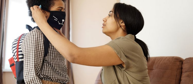 mother-putting-a-face-mask-on-her-son-4261265
